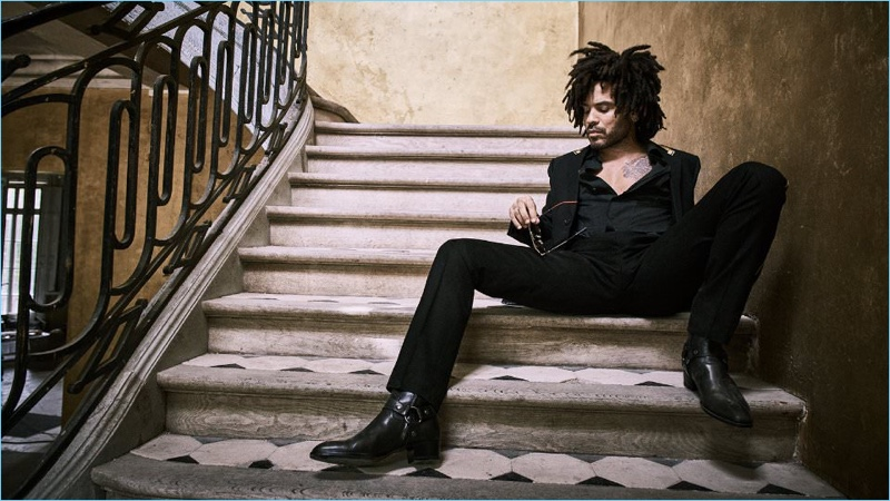 Relaxing, Lenny Kravitz wears a Saint Laurent blazer, trousers, and boots with a Haider Ackermann overshirt.