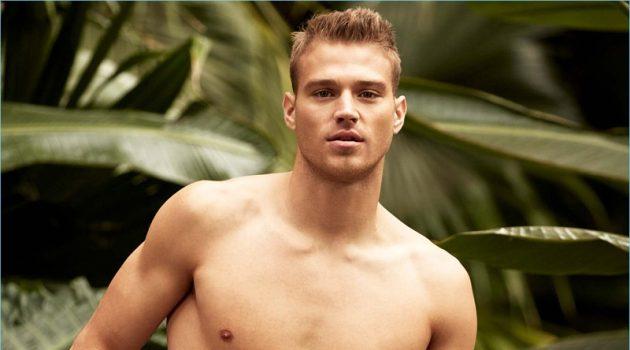 American model Matthew Noszka sports I.FIV5 satiny minimalist swim shorts with a playful print.