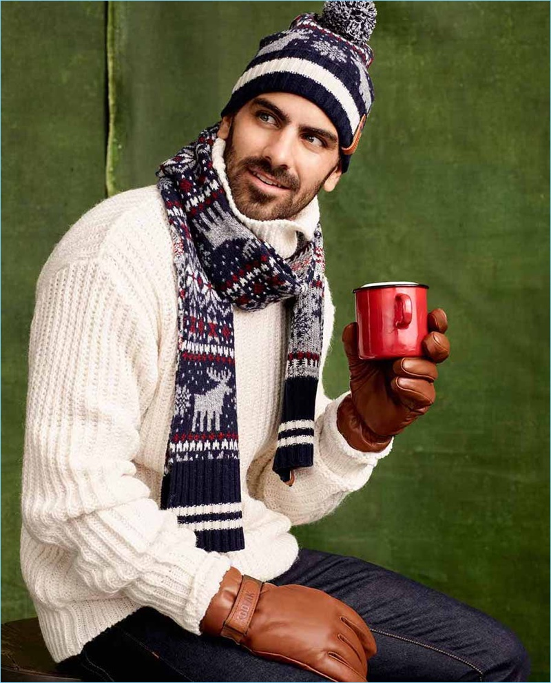 Reuniting with Simons, Nyle DiMarco sports a reindeer print scarf with a sweater and knit beanie by LE 31. He also wears Kodiak sherpa-lined leather gloves.