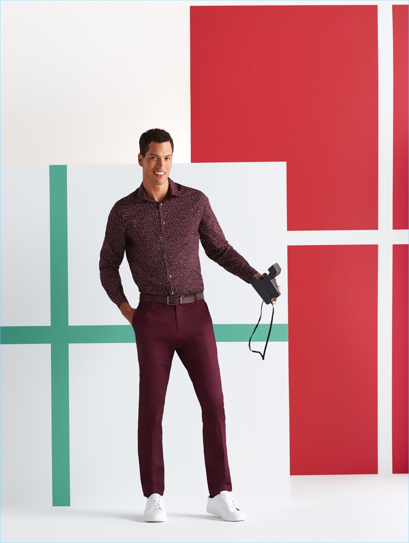 Family Holiday Photo: Model Chris Moore wears a Perry Ellis print shirt, suit pants, and white sneakers.