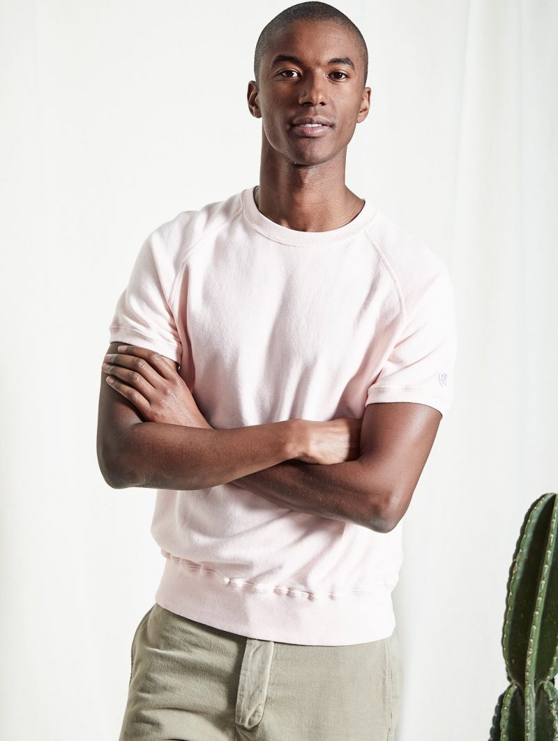 Model Claudio Monteiro wears a Todd Snyder + Champion short-sleeve sweatshirt and Todd Snyder selvedge chinos.