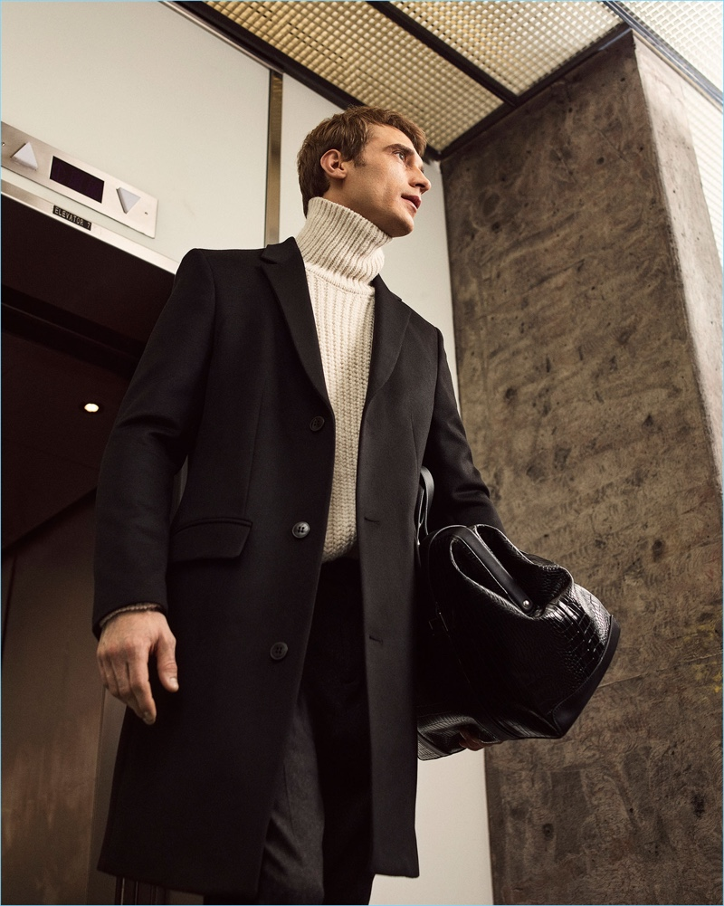 French model Clément Chabernaud dons a Zara Man overcoat and turtleneck sweater.