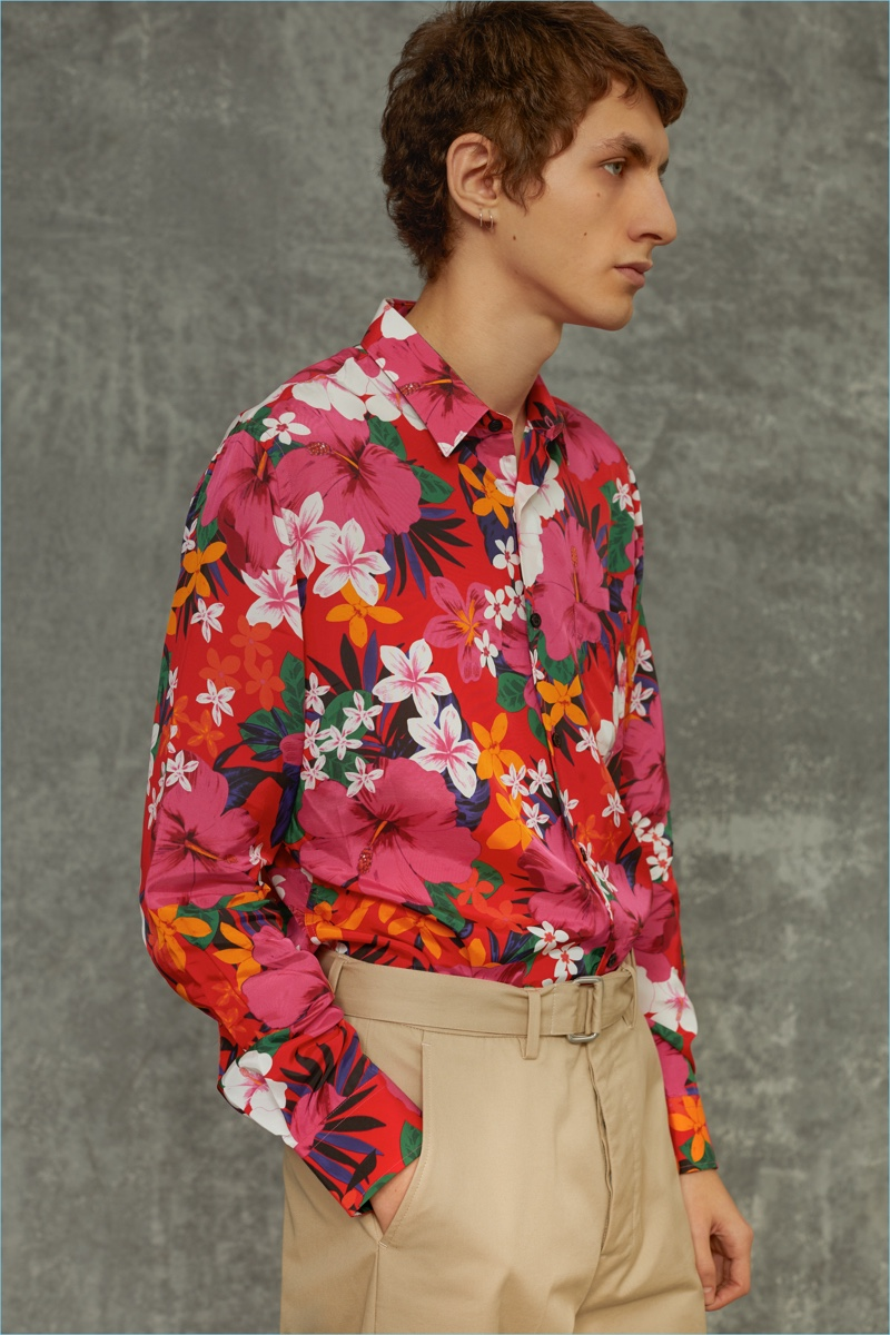 Delivering a side profile, Henry Kitcher wears a Hawaiian print shirt and pants by AMI.