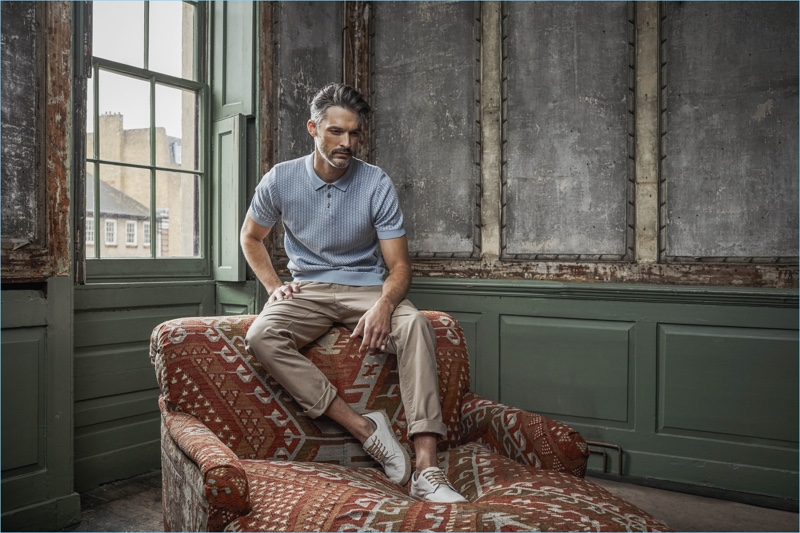 Embracing smart casual style, Ben Hill wears a polo with chinos and sneakers.