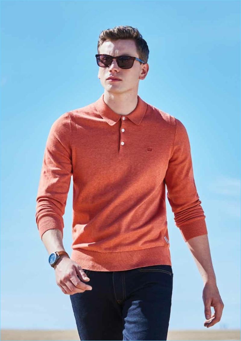 Model Sid Ellisdon sports a long-sleeve polo with dark wash jeans by Ben Sherman.