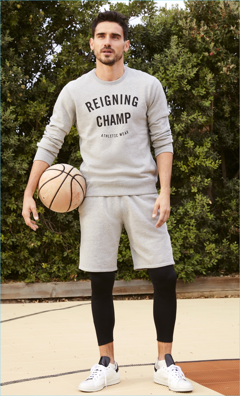 Ready for a game of basketball, Arthur Kulkov wears a Reigning Champ sweatshirt and shorts. The model layers with Halo tights and rocks Adidas by Raf Simons sneakers.