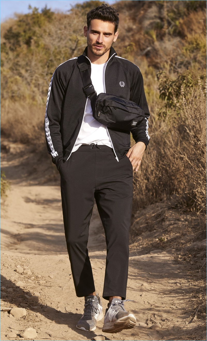 Going for a walk, Arthur Kulkov wears a Fred Perry track jacket with a Champion shirt, and DYNE pants. The top model also sports APL: Athletic Propulsion Labs sneakers and a Herschel Supply Co. hip pack.