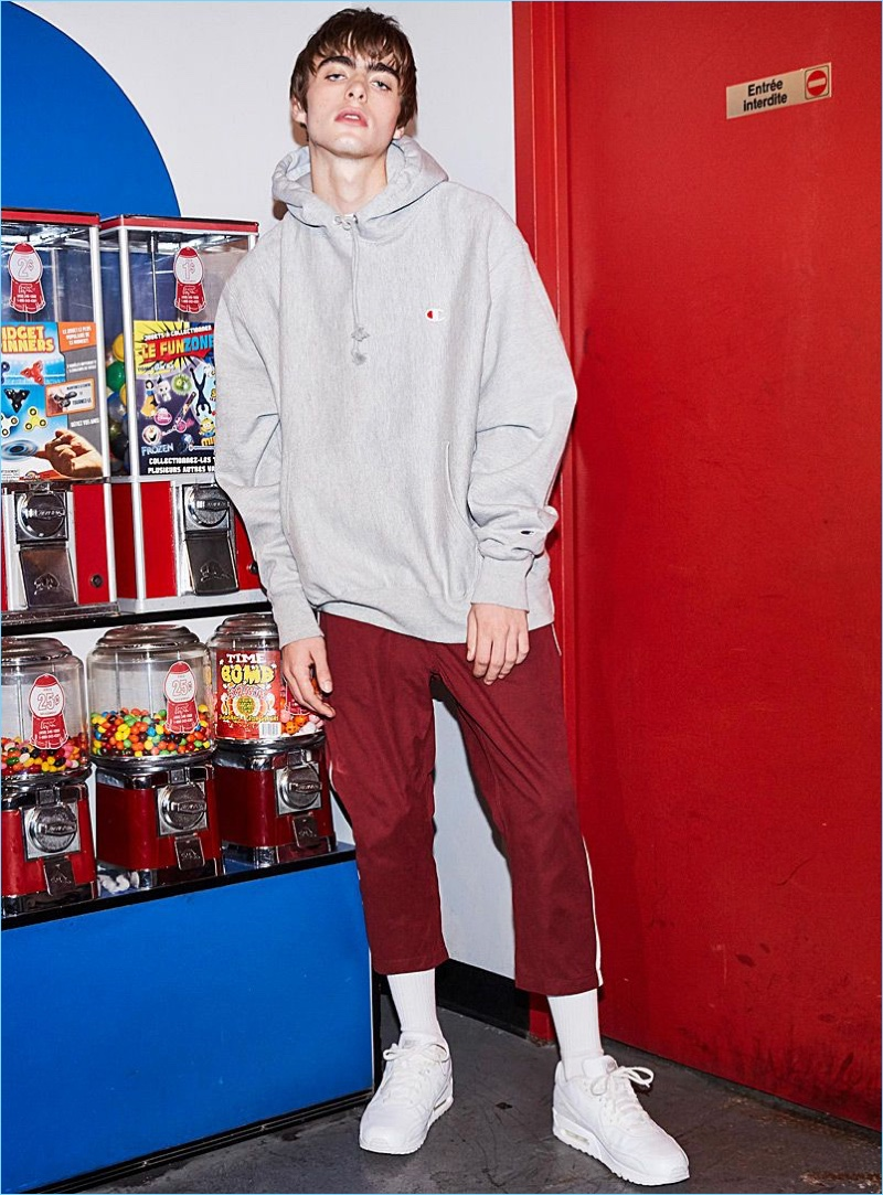 Sporting an oversized Champion hoodie, Lennon Gallagher also wears Fairplay track pants and Reebok Classic sneakers in white.