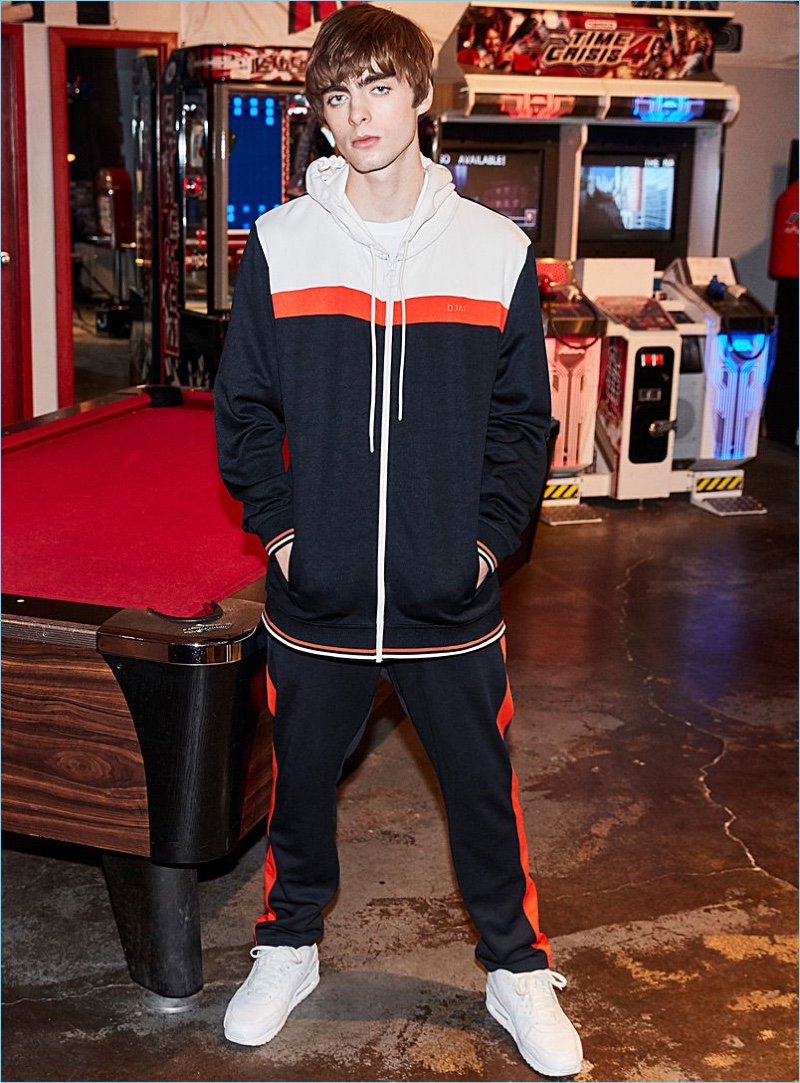 Lennon Gallagher rocks a DJAB athletic jacket and striped track pants with Reebok Classic sneakers in white.