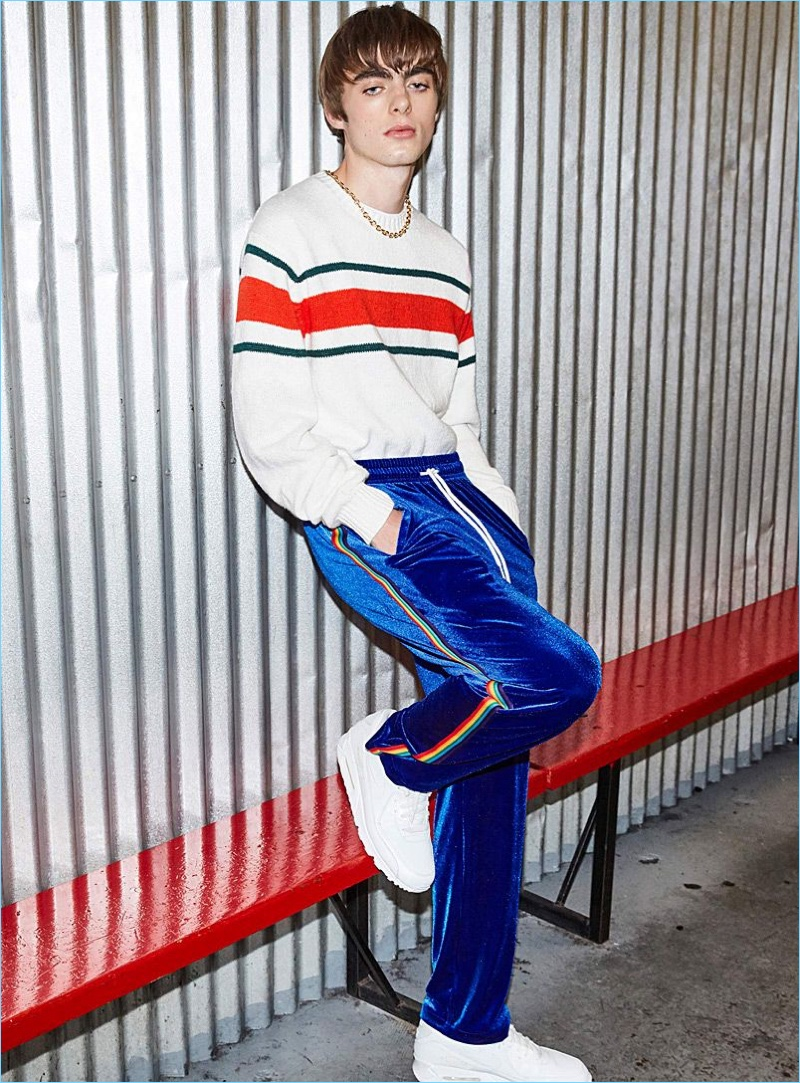 Embracing retro style, Lennon Gallagher wears a DJAB stripe sweater with IC.Story rainbow-stripe velvet track pants, and Nike Air Huarache Run Ultra sneakers.
