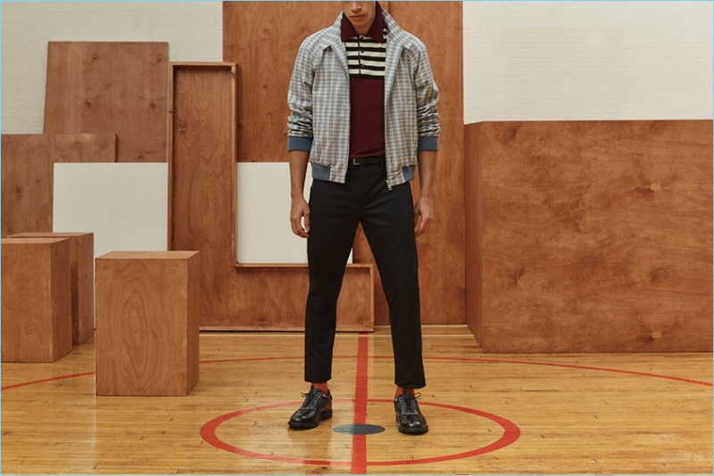 Prada offers a playful mix of patterns with a checked Harrington jacket, wool-flannel trousers, and a knit short-sleeve polo. It's styled with Prada wingtip brogues.