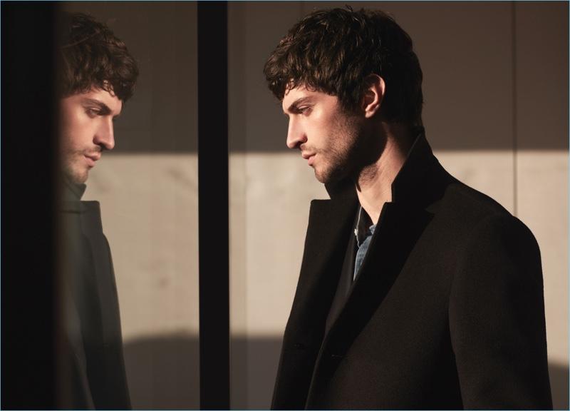 Matthew Bell dons a black overcoat with a denim grandad collar shirt by Reiss.
