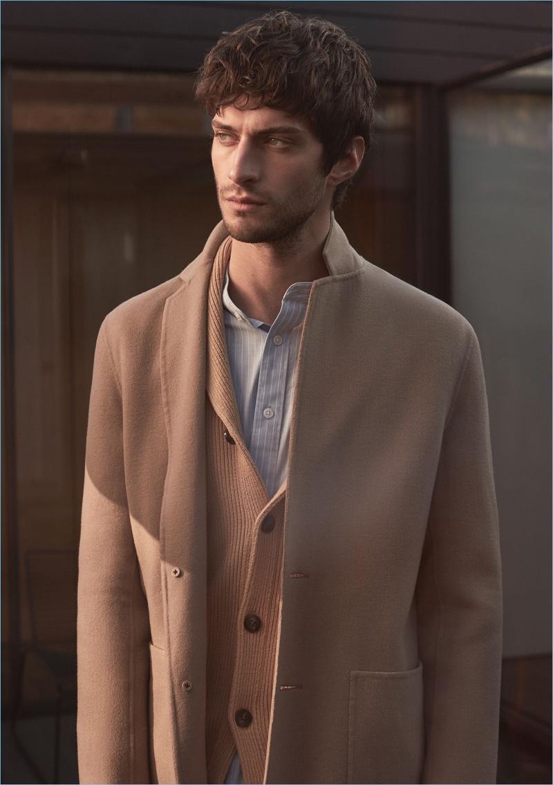 Layering neutrals, Matthew Bell sports a Reiss camel wool-blend overcoat and shawl-collar cardigan. He also wears a striped grandad collar shirt.