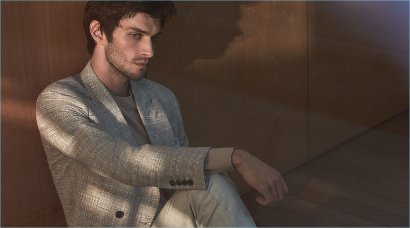 Suiting up, Matthew Bell dons a Reiss double-breasted blazer with a merino wool sweater and wool trousers.