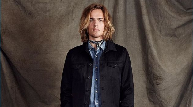 Scotch & Soda proposes elevated double denim with its Amsterdams Blauw label. Here, Ton Heukels wears a black denim trucker jacket with a light wash denims shirt. Cropped trousers polish up the timeless look.