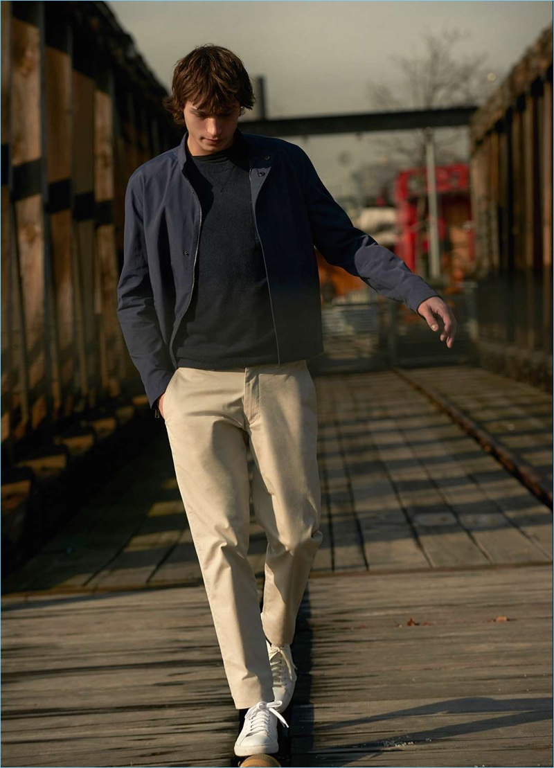 Embrace casual style with Club Monaco's tech moto jacket. Here, it's worn with a sweatshirt, chinos, and white leather sneakers.