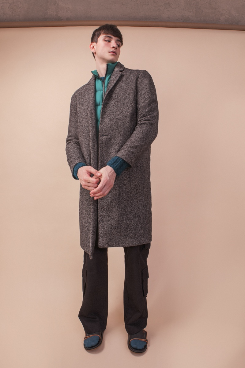Vitor wears coat Ermenegildo Zegna, sweater and vest B. Luxo, pants Another Place, socks Gucci, and sandals Rider.
