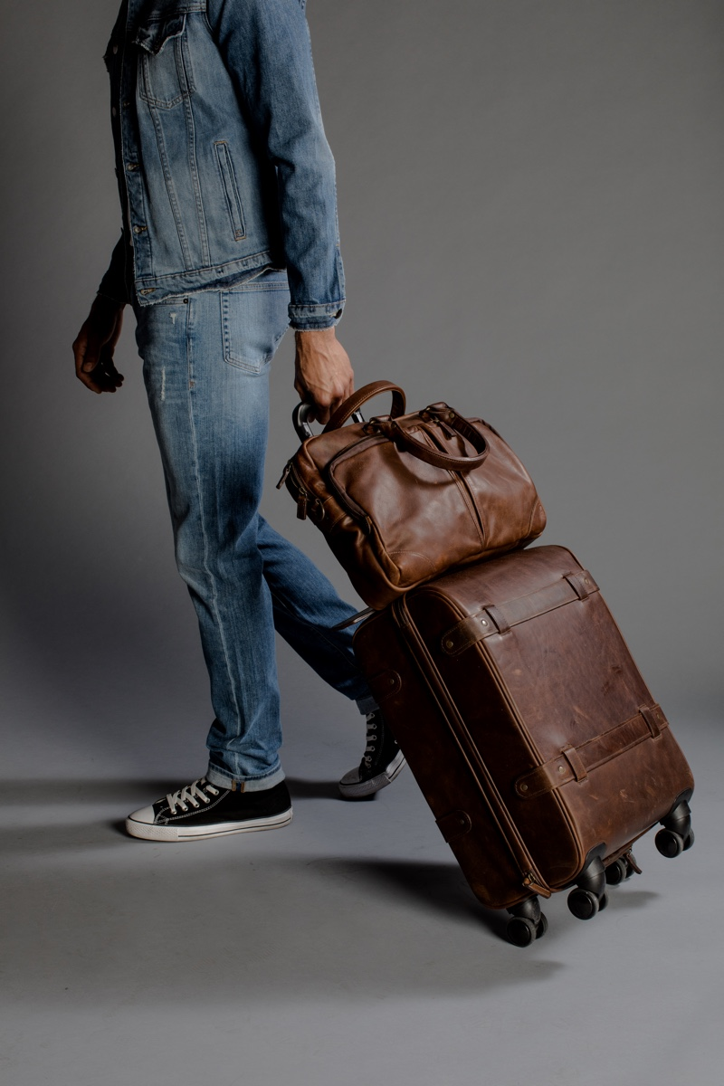 Zion wears shoes Converse, denim jacket and jeans Frame Denim. Travel bag set by Moore & Giles in saddle brown leather.