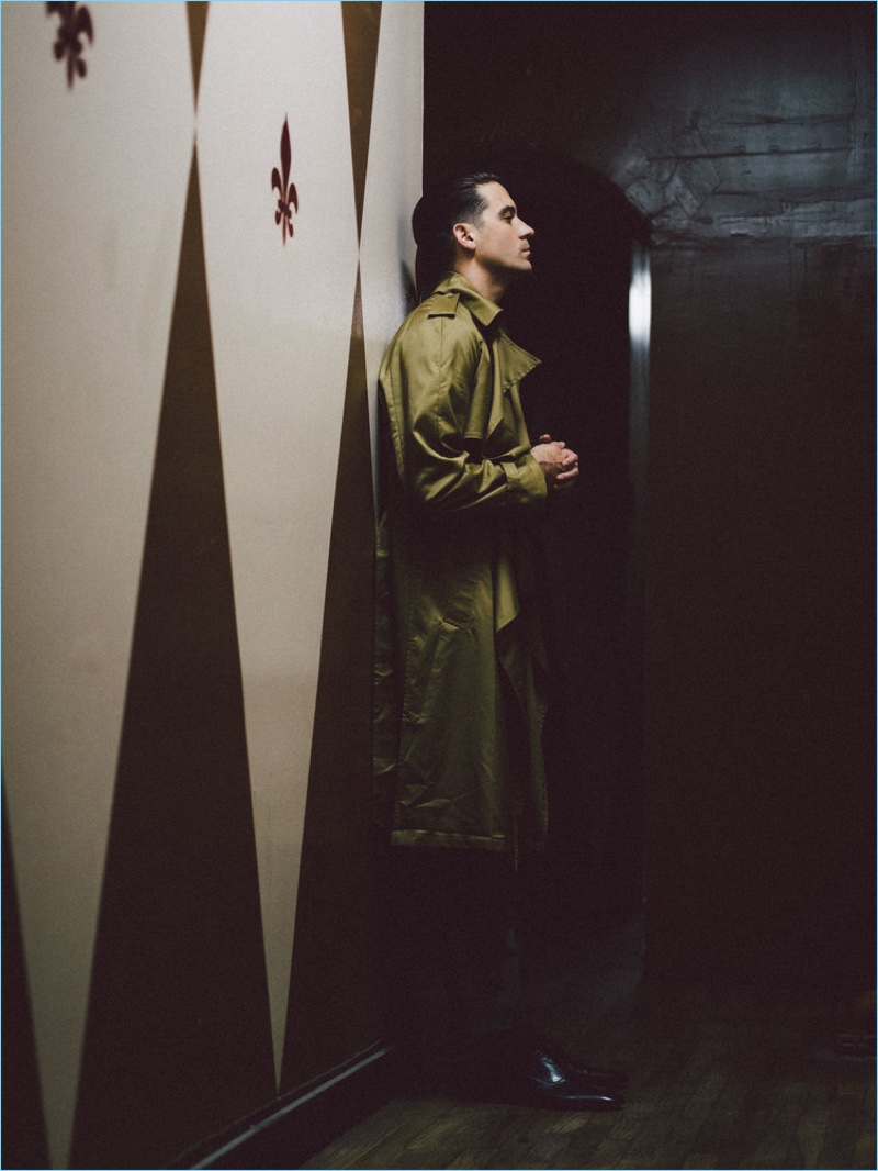 Delivering a side profile, G-Eazy wears a Louis Vuitton trench coat and trousers. He also sports Christian Louboutin shoes.