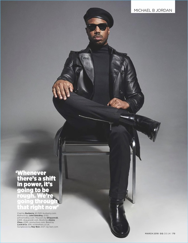 O ator do Panther preto, Michael B. Jordan, usa um casaco de couro Burberry com uma gola alta John Smedley.  Jordan também usa calças Dsquared2, Jimmy Choo boots e óculos de sol Ray-Ban.