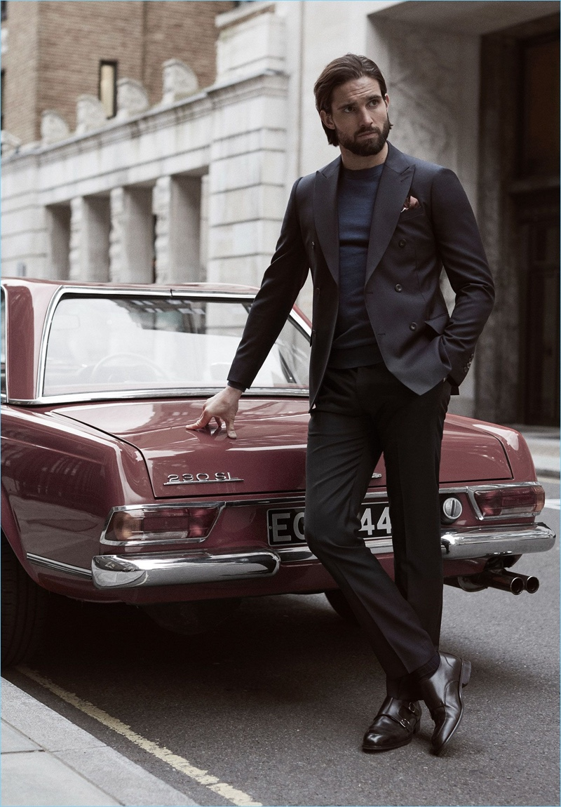 Stepping out in Reiss, Jamie Jewitt wears a double-breasted blazer, sweater, trousers, double monk strap shoes, and a patterned pocket square.