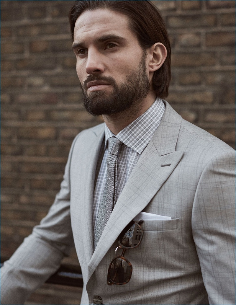 Donning shades of grey, Jamie Jewitt wears a Reiss suit, check shirt, tie, and sunglasses.