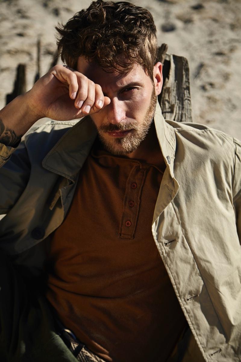 Benjamin wears trench POLO Ralph Lauren, long-sleeve tee Henry Cotton's, belt Levi's, and pants Giorgio Armani.