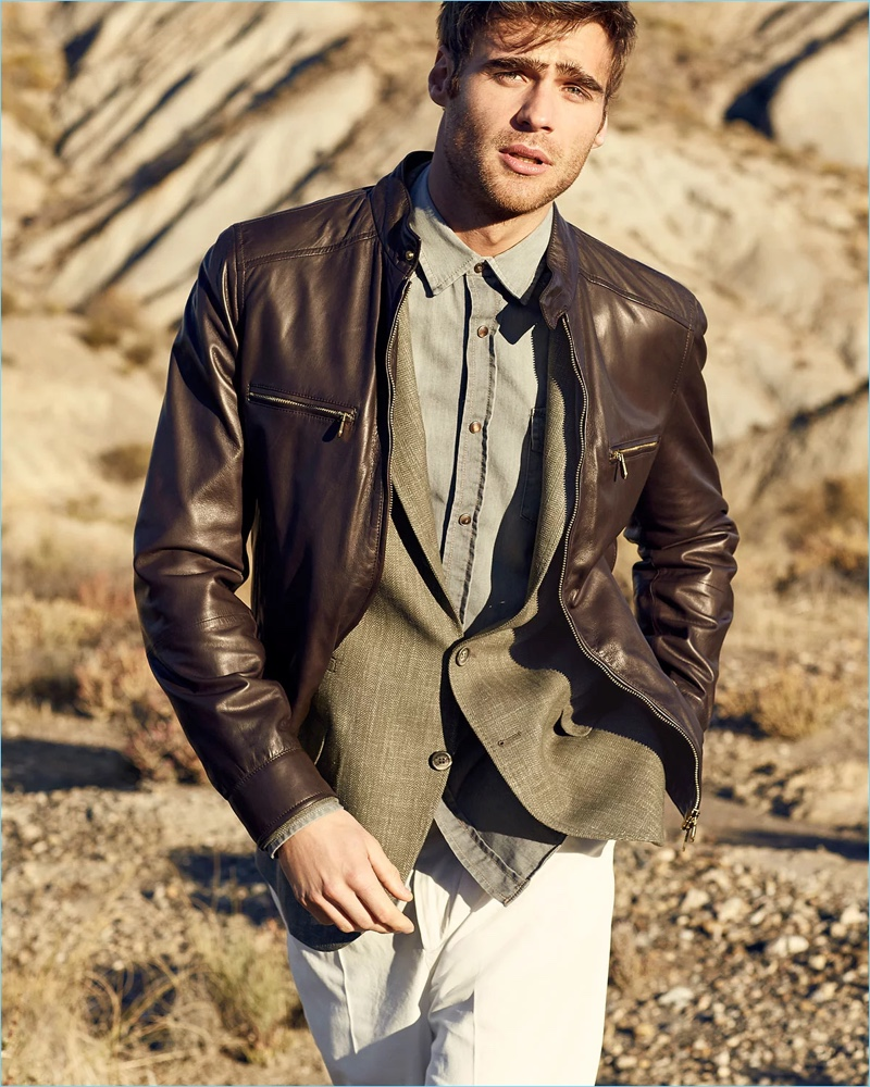 George Alsford is a sleek vision in Brunello Cucinelli. He wears a leather jacket with a herringbone sport jacket. The British model also dons the brand's denim western shirt and trousers.