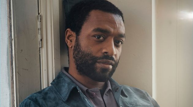 Sitting for a photo, Chiwetel Ejiofor dons a Tom Ford t-shirt and suede jacket. The actor also wears a Dries Van Noten shirt and Berluti trousers.