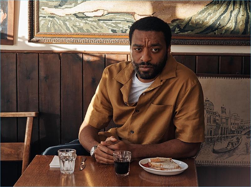 Starring in a photo shoot, Chiwetel Ejiofor wears an IWC Schaffhausen watch, Margaret Howell linen shirt, Sandro t-shirt, and Brunello Cucinelli trousers.