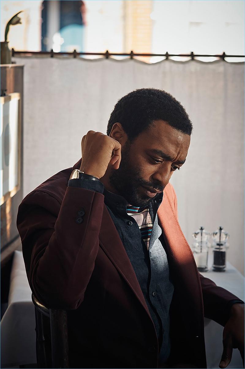 Actor Chiwetel Ejiofor sports an IWC Schaffhausen watch, P. Johnson jacket, Brunello Cucinelli linen shirt, and Prada sweater.
