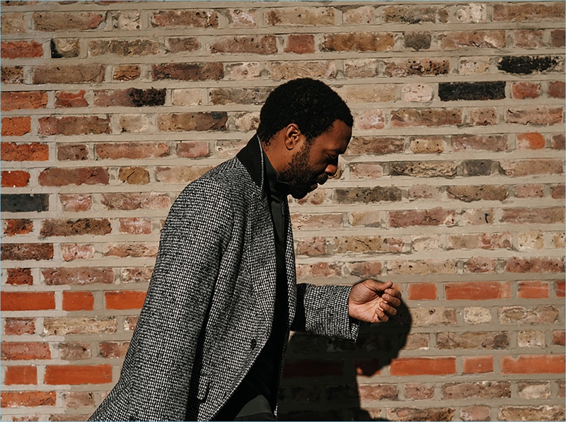 Delivering a side profile, Chiwetel Ejiofor wears a Salle Privée overcoat with an Ermenegildo Zegna sweater.