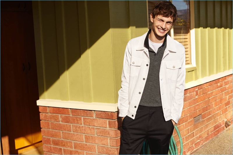 All smiles, Luc Defont-Saviard wears a H&M white denim jacket with a polo, t-shirt, and slim-fit chinos.