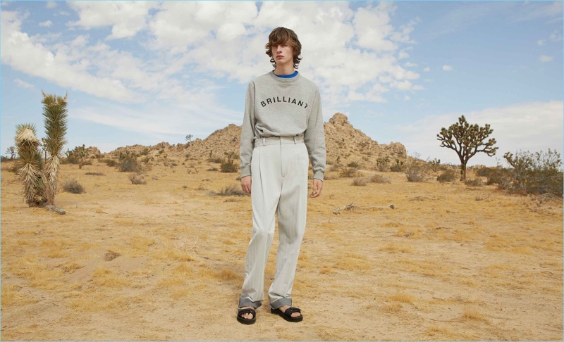 Taking to the desert, Benno Bulang wears a box logo sweatshirt and print t-shirt by A Brilliant Brand. Going monochromatic, he also sports Tarkek Classic cotton trousers by GmbH with Maison Margiela multi-strap leather sandals.