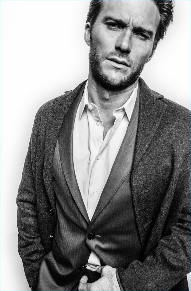 Appearing in a black and white photo, Scott Eastwood wears a Salvatore Ferragamo suit. He also dons an Acne Studios coat and Giorgio Armani shirt.