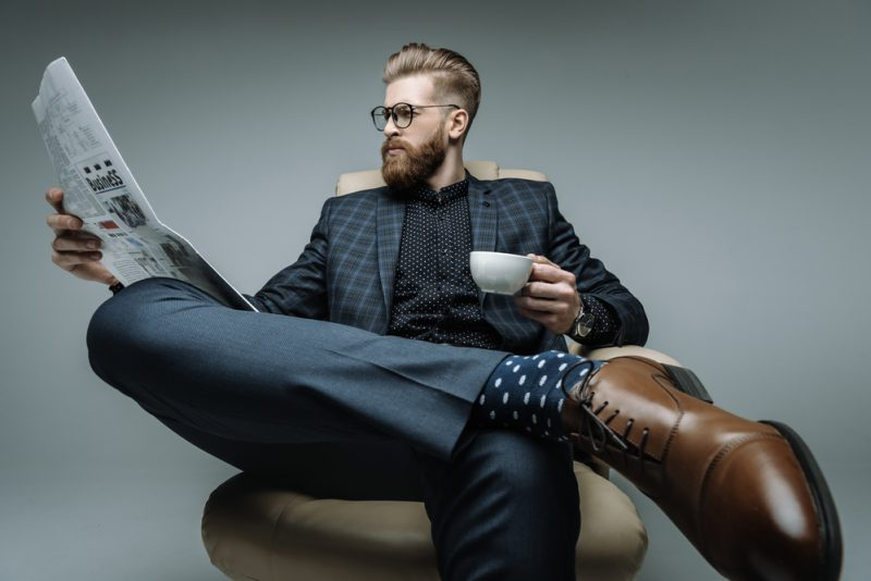 Stylish Man in Suit Reading Newspaper