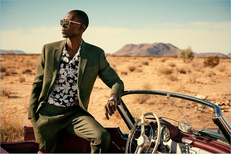 Armando Cabral models Todd Snyder's Sutton linen suit in olive. He also wears a camp collar floral print shirt.