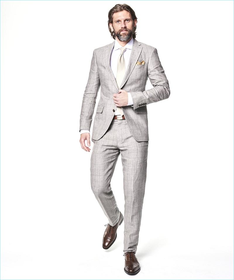 Tapping into a dapper edge, RJ Rogenski sports a Todd Snyder White Label Sutton windowpane linen suit in grey.