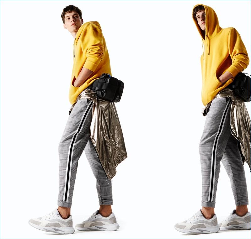 8c6a231e Model Frederik Ruegger wears a yellow sweatshirt, check trousers, a  metallic jacket, belt