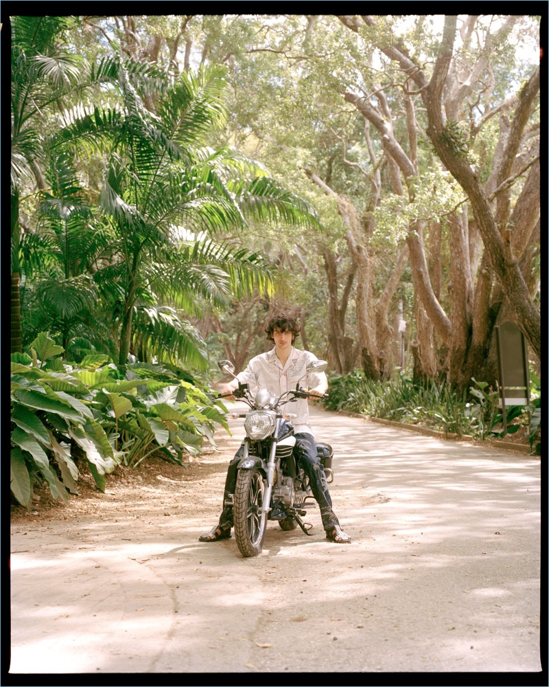 Taking a ride, Luca Lemaire wears a shirt and pants by Alexander McQueen with Prada sandals.