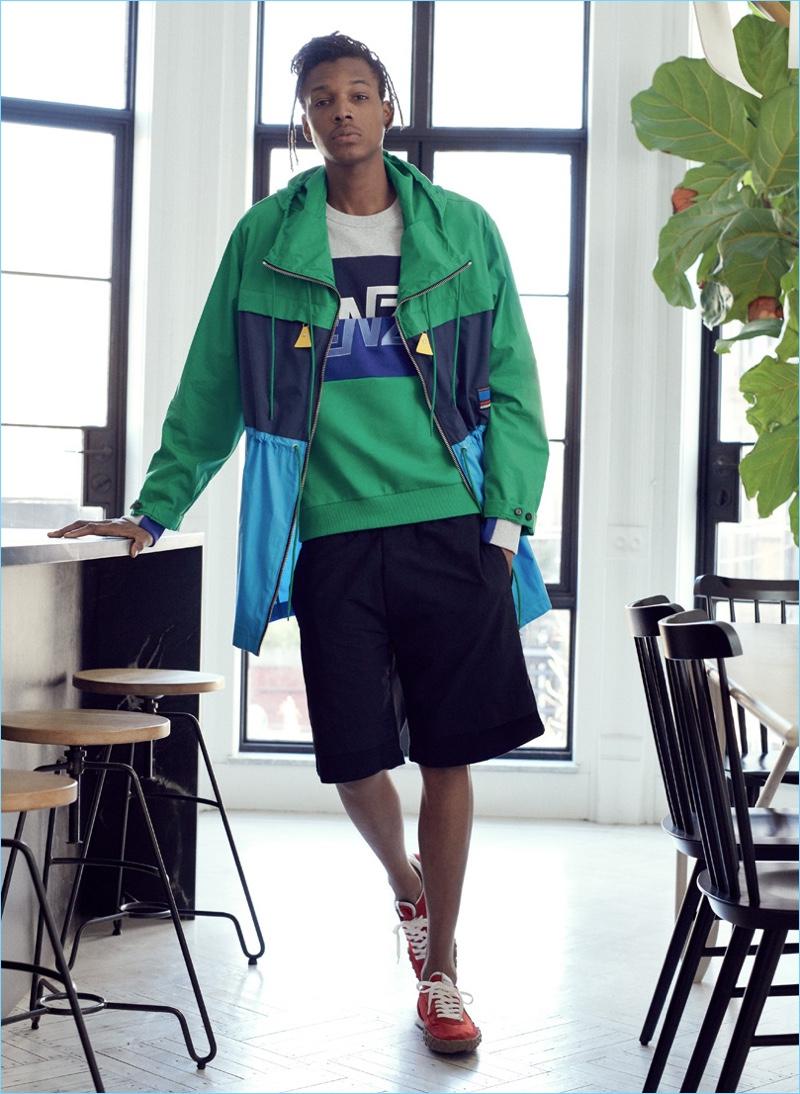 Going sporty, Matthew Davidson wears a parka, shorts, sweatshirt, and sneakers from Kenzo.