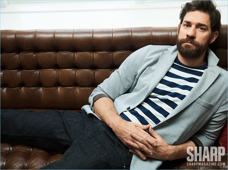 Lounging, John Krasinski wears an Eleventy jersey blazer, striped Rag & Bone t-shirt, and Ermenegildo Zegna pants.