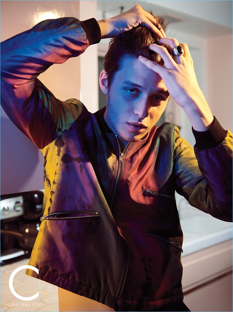 Fixing his hair, Nick Robinson wears a Saint Laurent bomber jacket.
