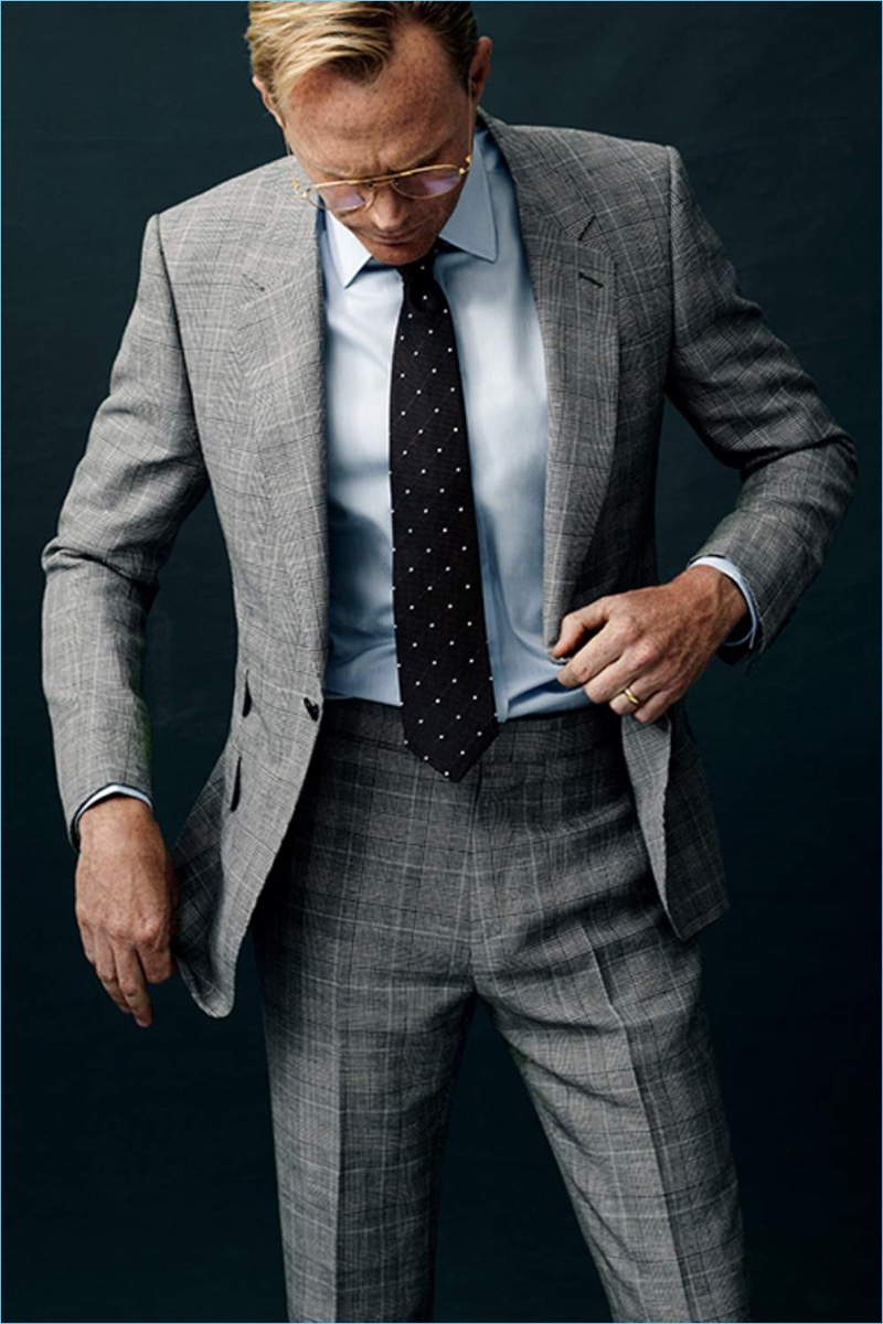 Dressed to impress, Paul Bettany wears a Kingsman grey Prince of Wales suit jacket and pants with a Kingsman + Turnbull & Asser herringbone shirt. Bettany also dons a Kingsman + Drake's polka dot tie and Kingsman + Cutler and Gross aviator-style optical glasses.