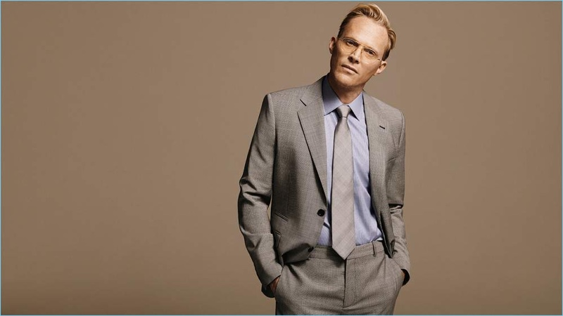Donning grey, Paul Bettany wears a Stella McCartney virgin wool blazer and trousers with a Kingsman + Turnbull & Asser blue linen shirt. The actor also dons a Kingsman + Drake's checked silk tie and Kingsman + Cutler and Gross aviator-style optical glasses.
