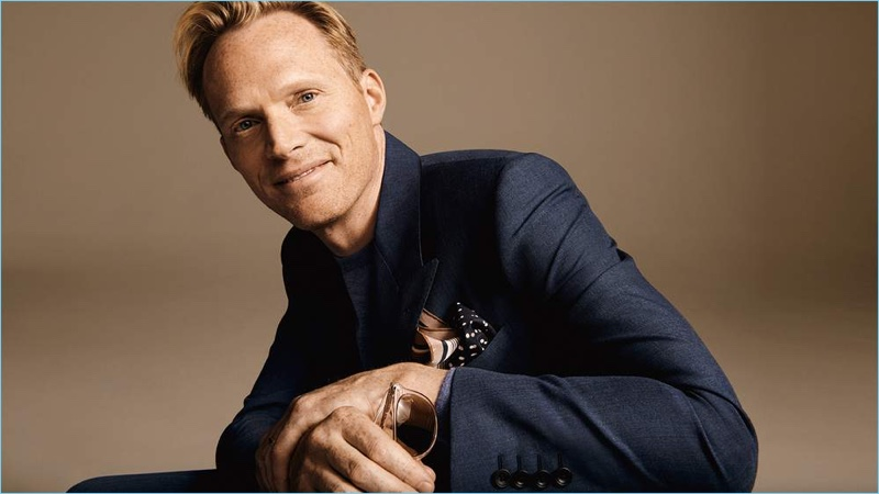 Paul Bettany wears a Kingsman sweater and double-breasted suit jacket. He accessorizes with Saint Laurent sunglasses and a Dries Van Noten printed silk pocket square.