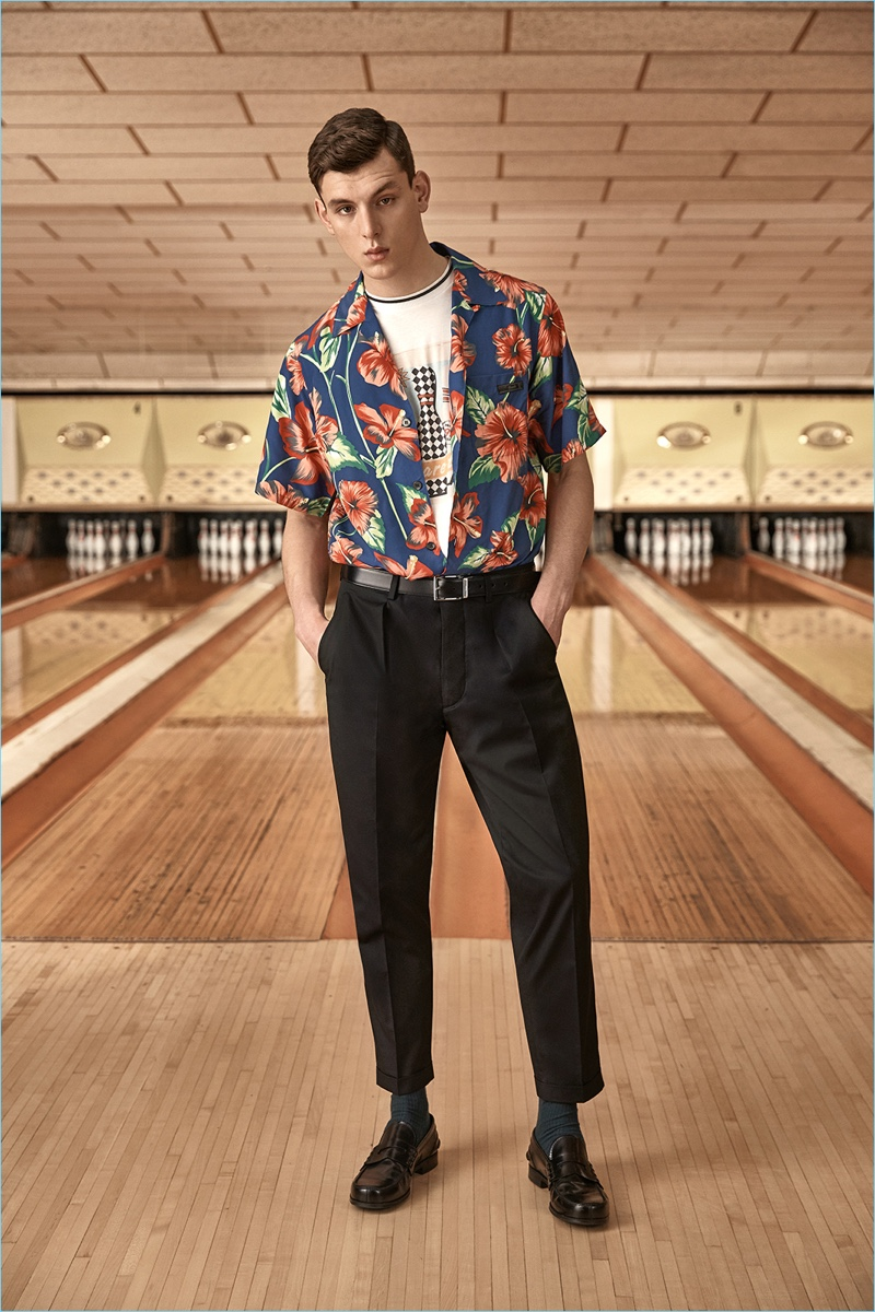 Ready for a summer holiday, Luke Farley wears a tropical print camp collar shirt from Prada. He also sports the label's graphic tee and tapered trousers.