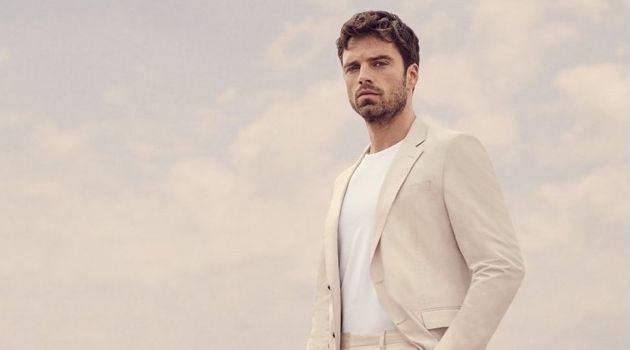 """Donning a neutral suit, Sebastian Stan takes to the beach for BOSS' """"Summer of Ease"""" campaign."""