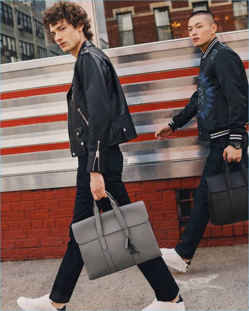 Left to Right: Serge Rigvava wears a Coach 1941 moto jacket in black. Satoshi Toda models a Coach 1941 patchwork varsity jacket. Both models carry Coach's Metropolitan Portfolio leather bag.