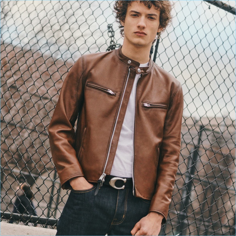 Serge Rigvava rocks a brown leather racer jacket by Coach 1941. He also sports the brand's sculpted signature belt.
